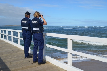 A male and female fisheries officer standing on a wharf looking out to sea.