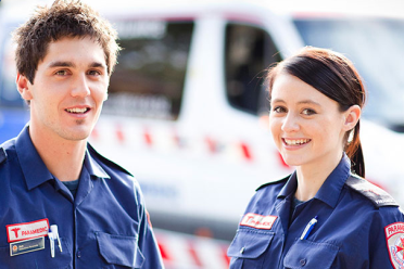 A young male and female paramedic standing in front of an ambulance.