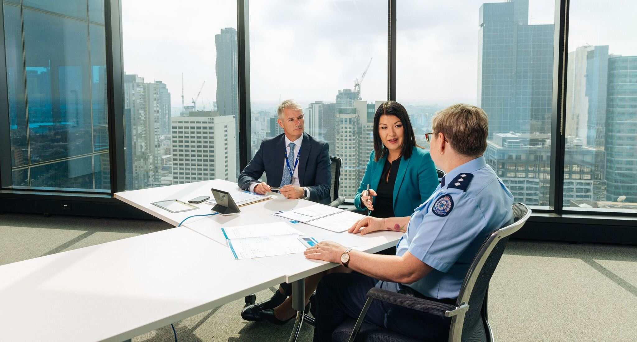 A female executive director with male and uniformed female colleague in discussion in a meeting room.